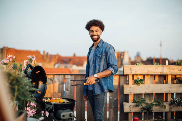 młody człowiek gotuje na grillu na imprezie na dachu - grillowany zdjęcia i obrazy z banku zdjęć