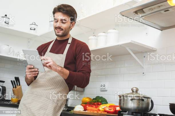 Young man cooking romantic dinner at home using digital tablet picture id1169041529?b=1&k=6&m=1169041529&s=612x612&h=7wxb912p6qjtbjmdjy2l4iybcoxeyholof4aupl836q=