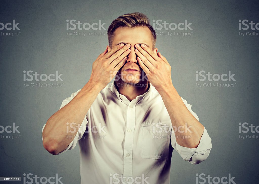 Young man covering eyes with both hands stock photo