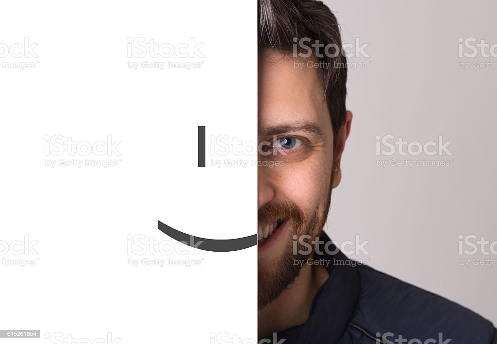 Young man covering half his face with a smiling emoticon stock photo
