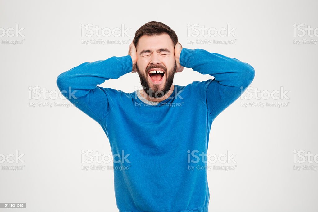 Young man covering his ears and screaming stock photo