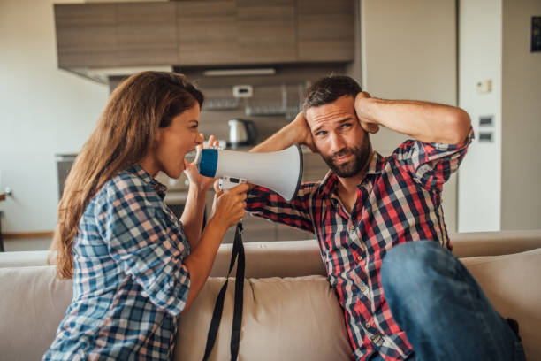 Young man covering his ears while a woman yells at hm through megaphone Young couple using megaphone while arguing at home hands covering ears stock pictures, royalty-free photos & images