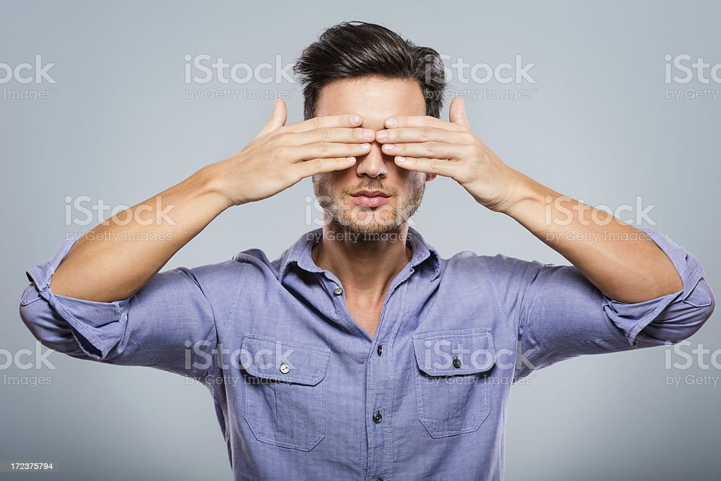 Young man covering his eyes stock photo