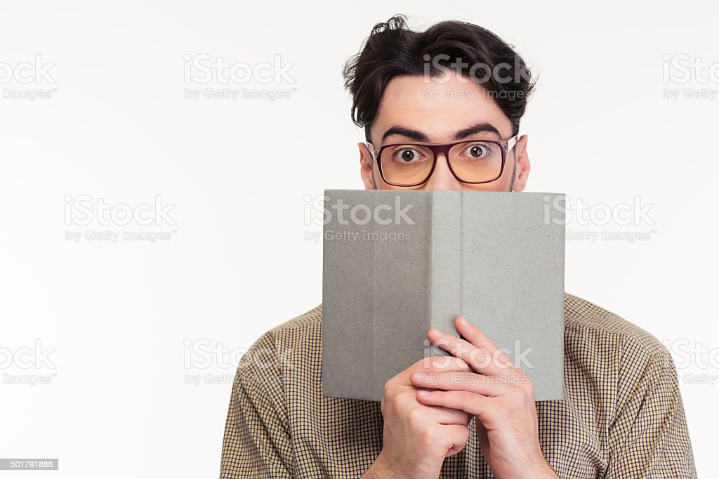 Young man covering his face with book stock photo