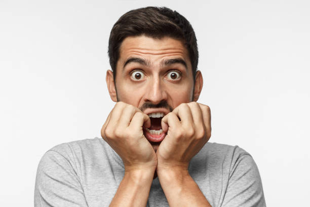 Young man covering mouth with hands and round eyes, experiencing deep astonishment and fear, isolated on gray background stock photo