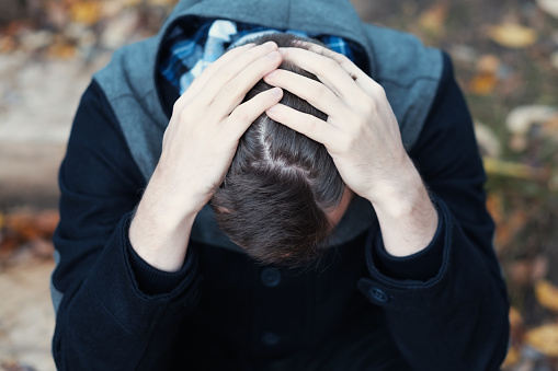 Young Man Covers His Face With His Hands In Grief Stock Photo - Download Image Now