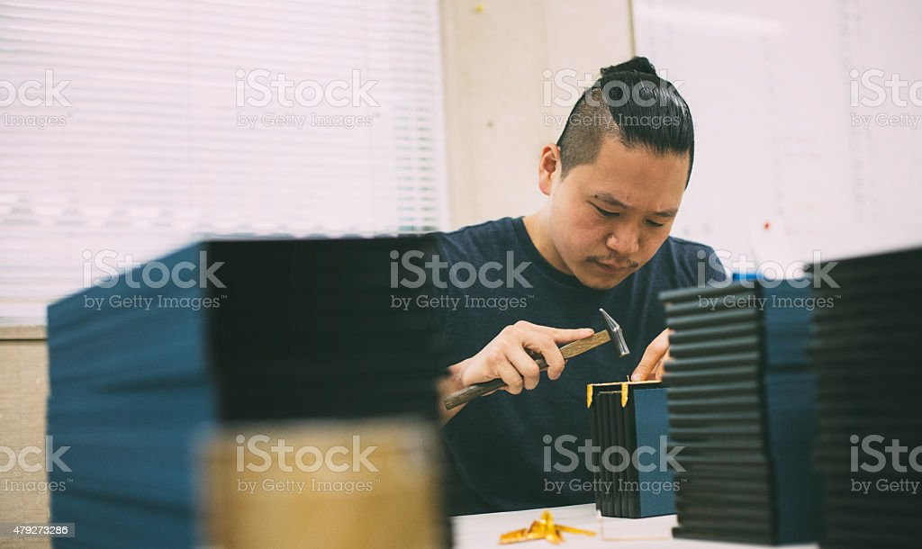 Young man creating a wooden craft box. He is working with hammer. He...