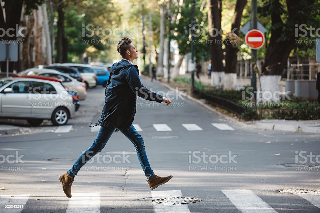 Young man cross the street stock photo