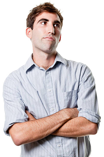 Young Man Crosses Arms and Looks Away Portrait of a young man on a white background. rolling eyes stock pictures, royalty-free photos & images