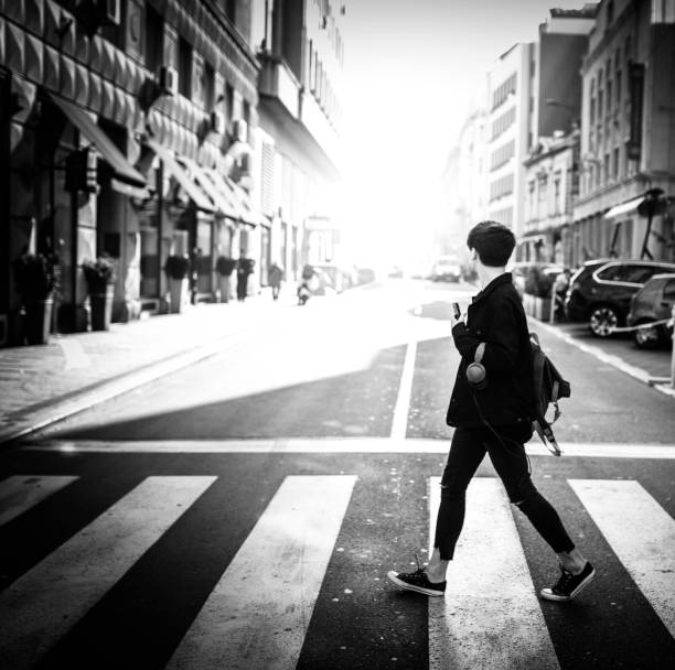 Young man crossing a city street