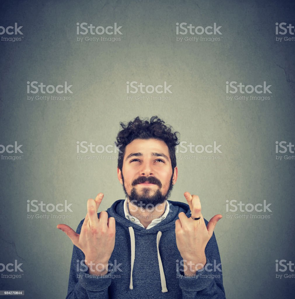 Young man crossing fingers and making a wish stock photo
