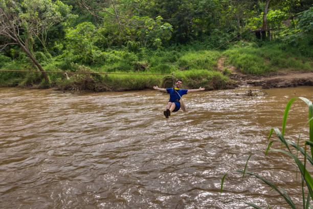 junger mann, die überquerung des flusses auf zip-line in chiang mai thailand - zip hoodies stock-fotos und bilder