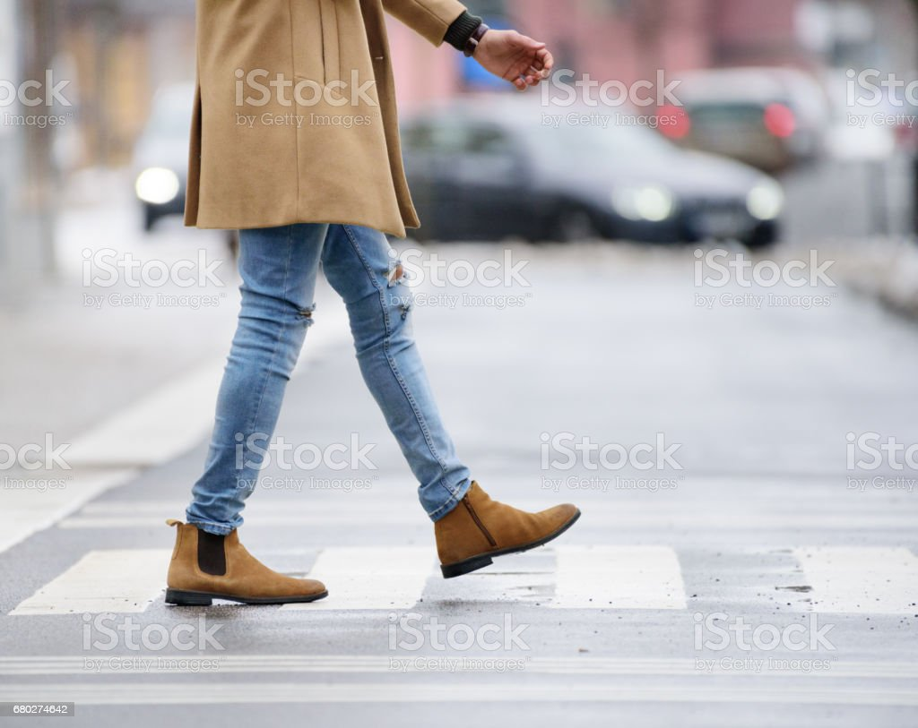Young man crossing winter street