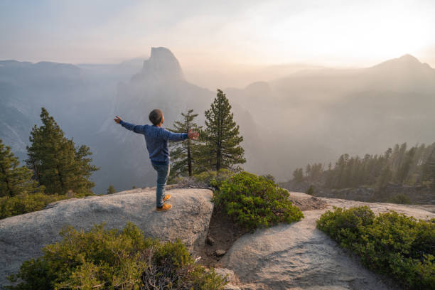 Young man cstamding arms outstretched on top of Yosemite valley, USA at sunrise stock photo