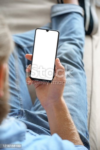 Young man customer choosing buying order in shopping app, reading social media news, texting mobile sms message in chat, using smart phone mock up blank screen sit on sofa. Vertical over shoulder view