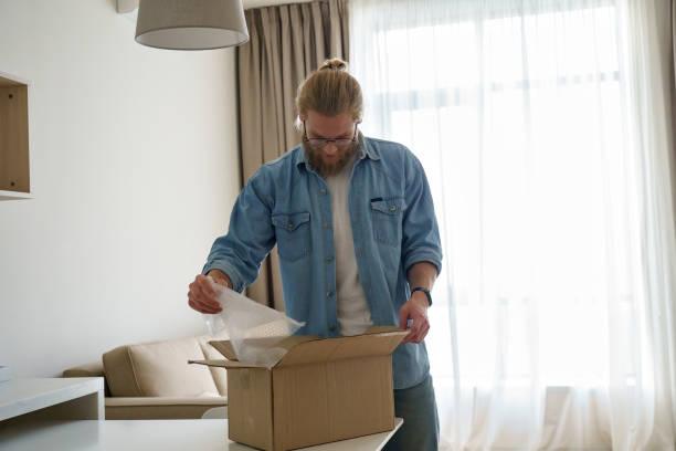 Young man customer unpacking cardboard box receive open post mail picture id1221338474?b=1&k=6&m=1221338474&s=612x612&w=0&h=nx mmptleoajl58kdzb2y1 xipg987xhahwnedzjv0y=