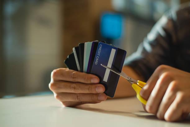 młody człowiek cięcia karty kredytowej z nożyczkami, człowiek niszczy karty kredytowe z powodu dużego zadłużenia. - ciąć zdjęcia i obrazy z banku zdjęć
