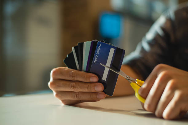 young man cutting credit card with scissors,man is destroying credit cards because of big debt. - dept stock pictures, royalty-free photos & images