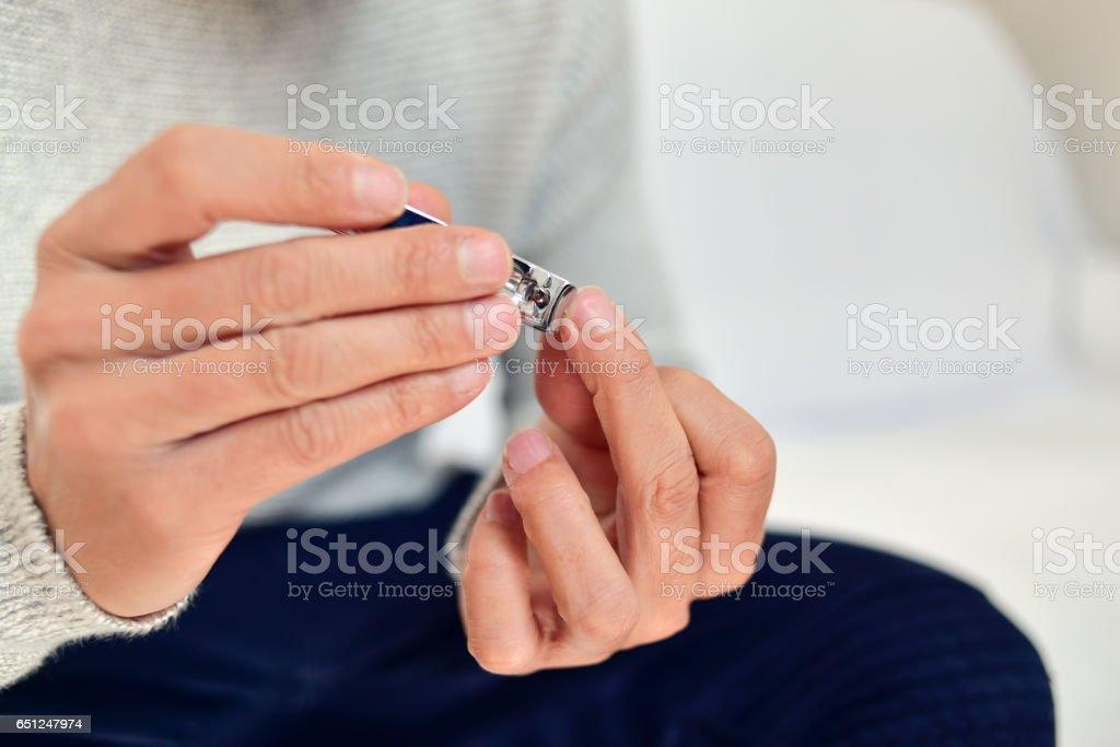 young man cutting his fingernails - foto de acervo