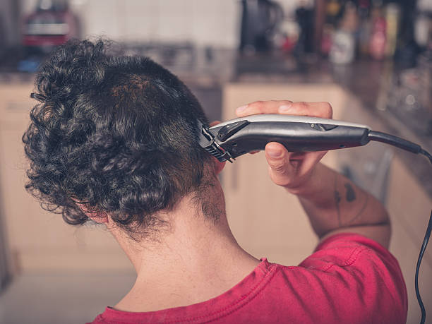 Young man cutting his hair at home stock photo