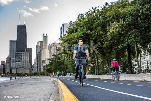Young man cycling in Chicago by Michigan lake, commuting to work, United States.