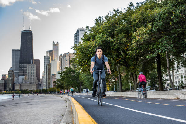 Young man cycling in Chicago by Michigan lake, commuting to work stock photo