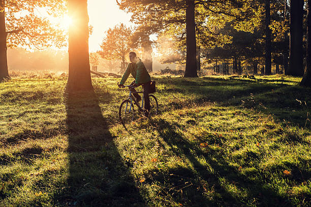 young man cycling in richmond park, london - richmond park stock photos and pictures