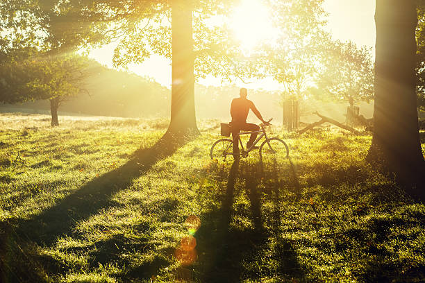 young man cycling in richmond park, london - sustainable travel stockfoto's en -beelden