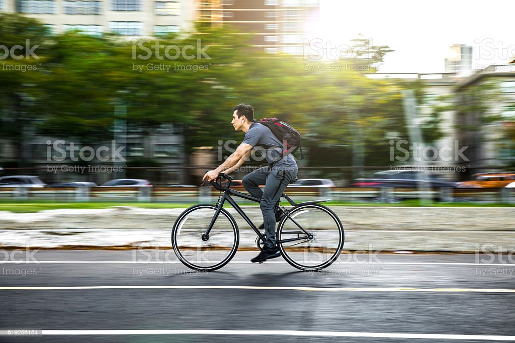 Young man cycling in the city, commuting to work – zdjęcie