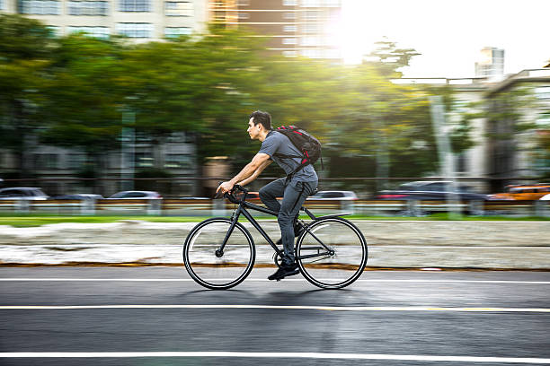 Young man cycling in the city, commuting to work stock photo