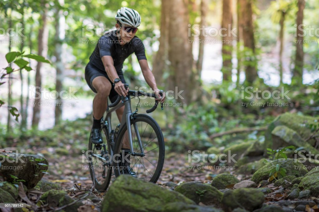 Young man Cyclist riding mountain bike in public park at morning stock photo