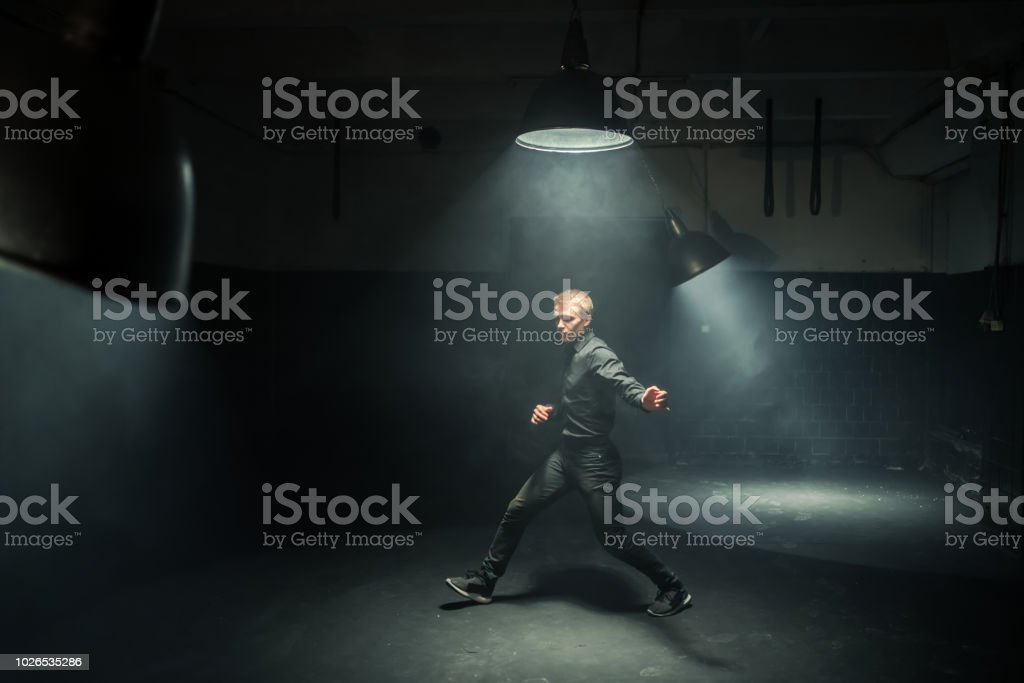 Handsome bearded man in black clothing dances the hip-hop. He is...