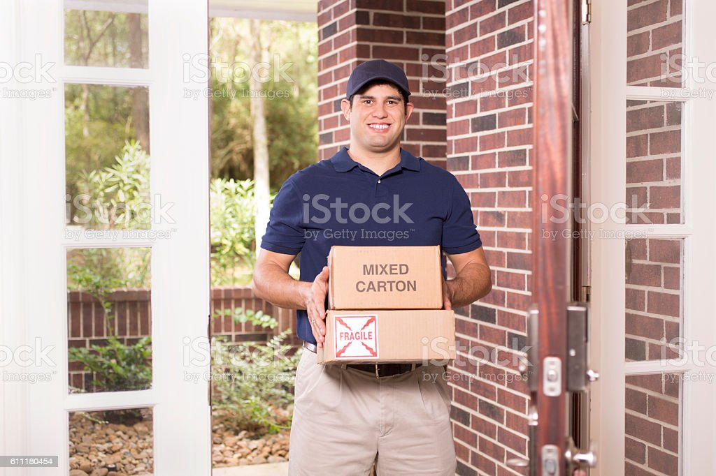 One young adult man wearing blue uniform delivers packages to...
