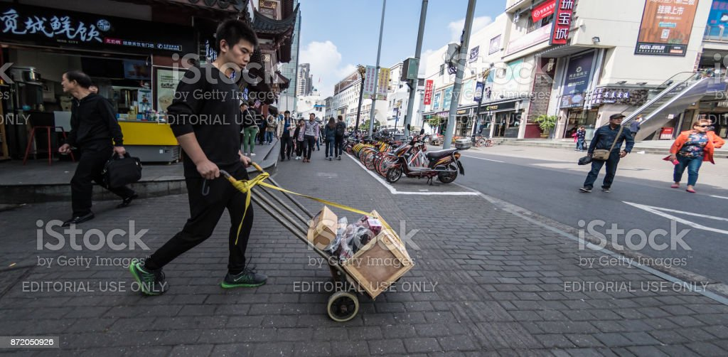 Young man delivers stock on trolley in Shanghai stock photo