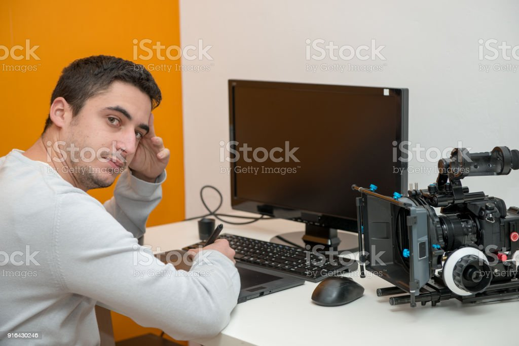 young man designer using graphics tablet for video editing stock photo