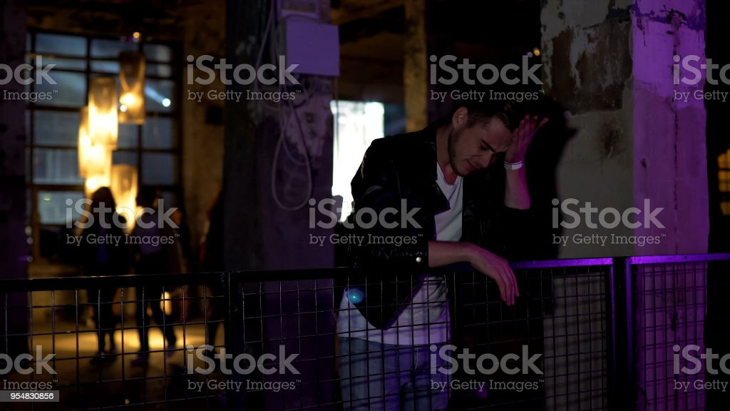 Young man desperately thinking about problems while standing at nightclub hall stock photo