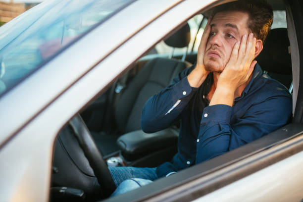 A young man desperately waits in the traffic jam stock photo