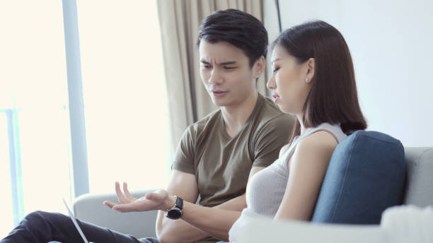 Young man discusses finances with wife Young man asks his wife a question while discussing finances. He is gesturing as he asks the question. They are looking at their online bank statement. asian couple arguing stock pictures, royalty-free photos & images