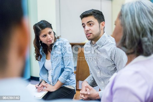 956725740istockphoto Young man discusses something during group therapy session 964284140