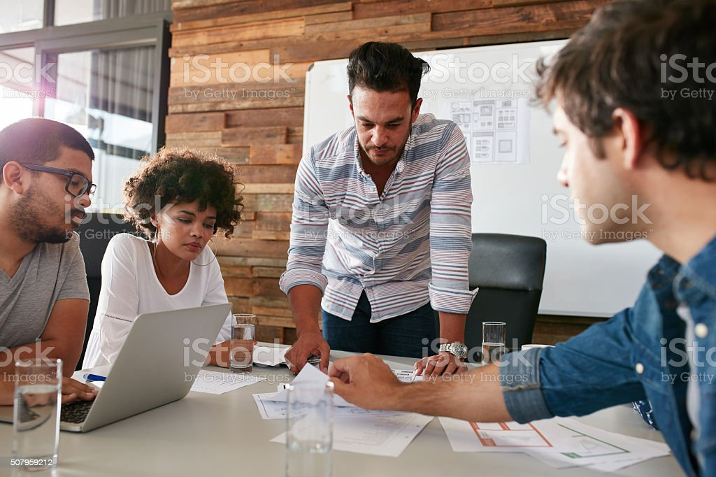 Young man discussing market research with colleagues stock photo