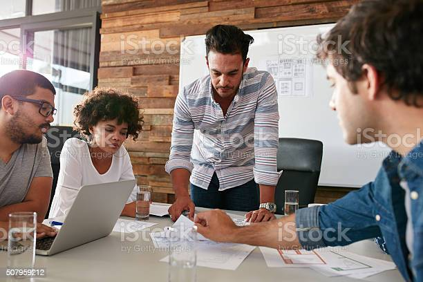 Young Man Discussing Market Research With Colleagues Stock Photo - Download Image Now