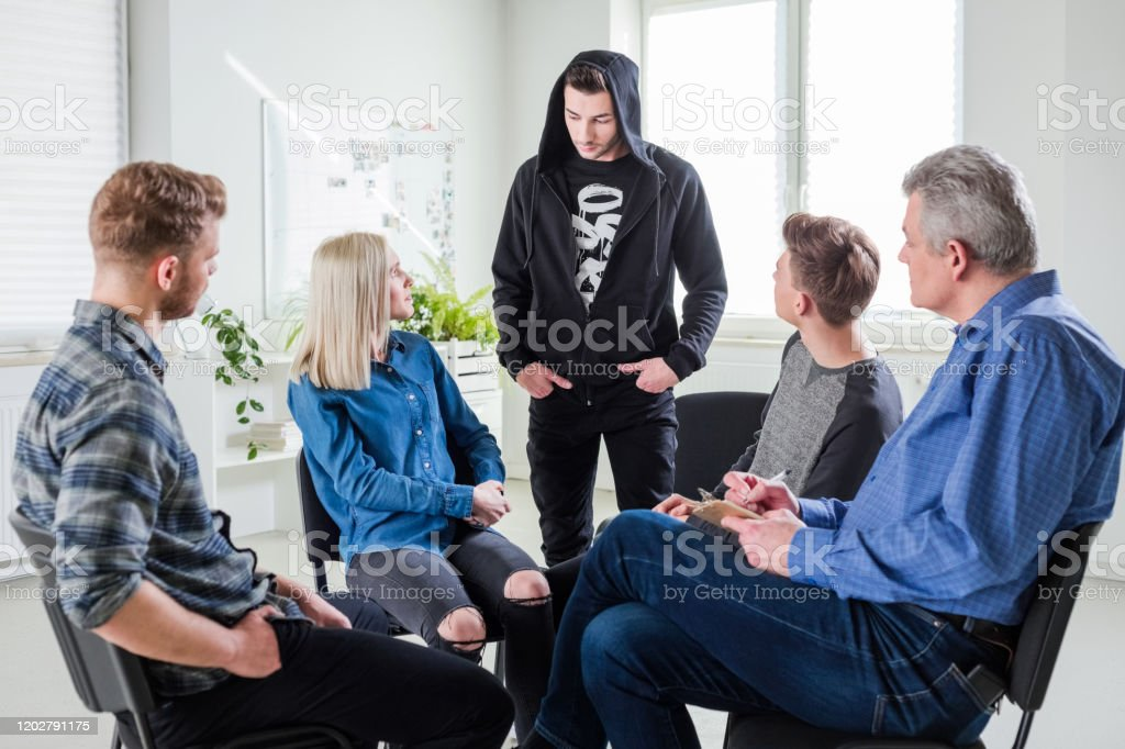 Young man discussing problems during group therapy Young man discussing problems with friends and mature social worker. Mental health professional is with young university students in lecture hall. They are in group therapy at university. 18-19 Years Stock Photo