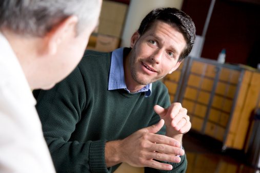 Young Man Discussing Something With A Friend Stock Photo - Download Image Now