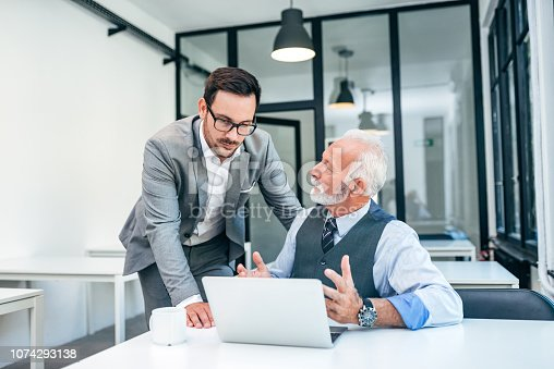 istock Young man discussing with boss or older employee in modern office. 1074293138
