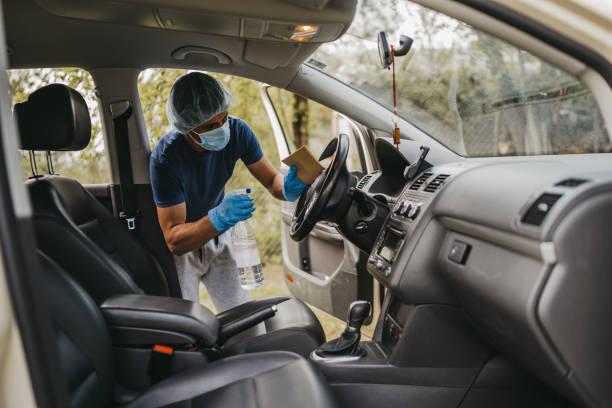 Young man disinfecting car interior stock photo