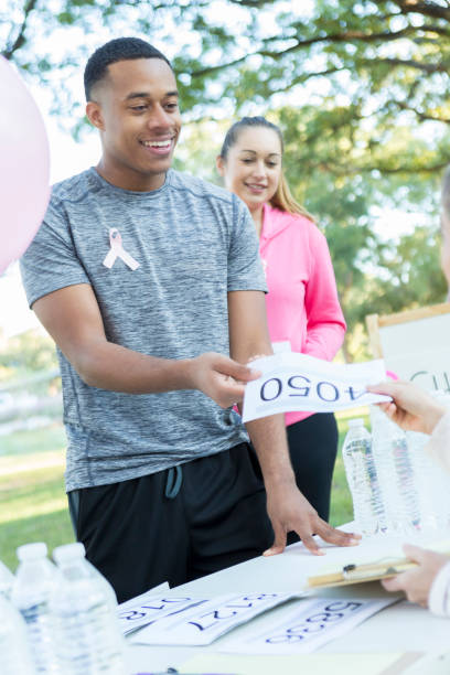 junger mann vertreibt sport lätzchen vor brust-krebs-rennen - leitungswasser trinken stock-fotos und bilder