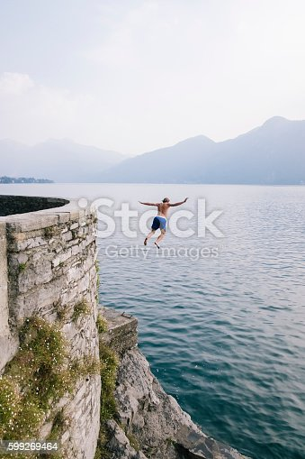 istock Young man diving in the water from a cliff. 599269464
