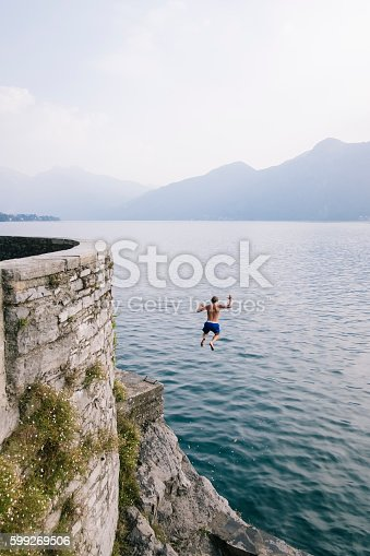 istock Young man diving in the water from a cliff. 599269506