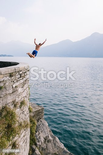 istock Young man diving in the water from a cliff. 599269588