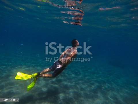 831127716 istock photo Young man diving underwater 942192812